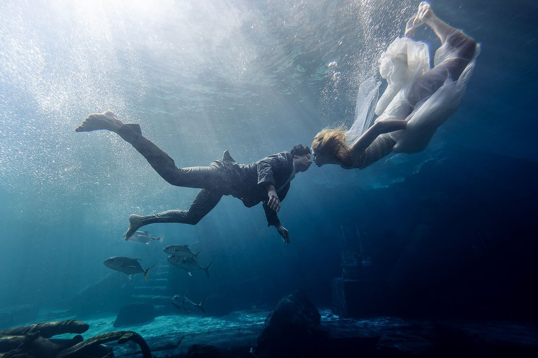 Bride and groom kissing under water